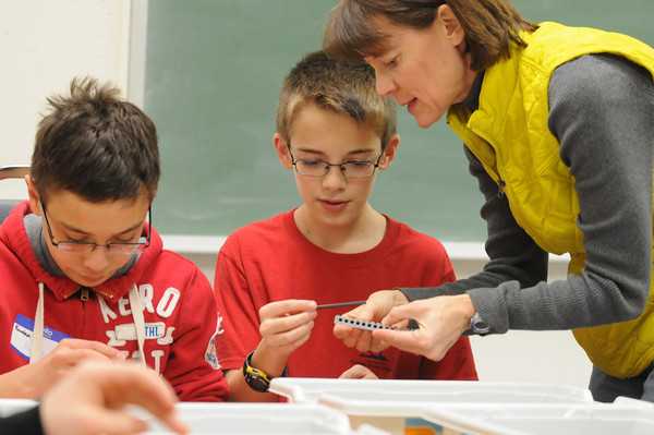 Instructor Deb Johnson gives Boy Scouts Ahn Enright (center) and Kawika Hashimoto a hand assembling their robot during a robotics camp sleep in for Scouts Friday at the Southern Minnesota Children's Museum in Mankato. Scouts could earn their robotics camp at the end of the sleep in after learning about sensors, assembly and programming of the Lego robots.