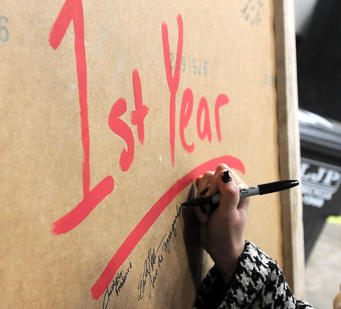 Visitors write messages on a giant board celebrating the Mankato Brewery's first anniversary.