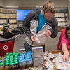 Andrew Gould (center) looks over pacifiers with help from Stacey Peterson (right) of Feeding Every Baby Formula Shelf while Caden Gould (left), 5, checks on his three-month old sister. Photo by Jackson Forderer