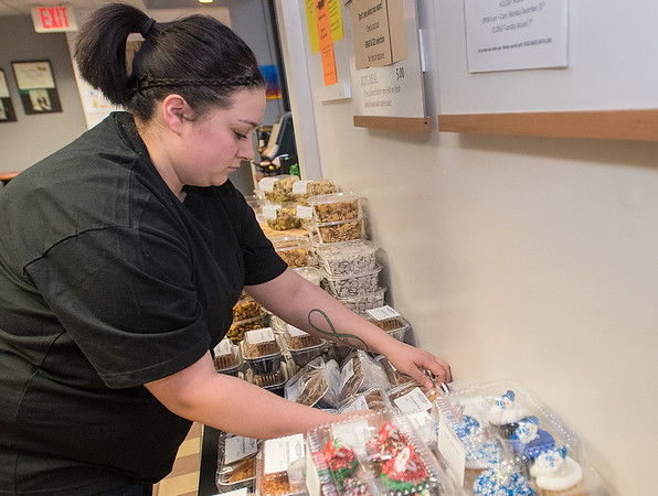Sam Cline, the catering manager and lead decorator for Wooden Spoon, arranges baked items for sale at Friesen's Bakery on Thursday. The business will change its name on Jan. 2 to Wooden Spoon. Photo by Jackson Forderer