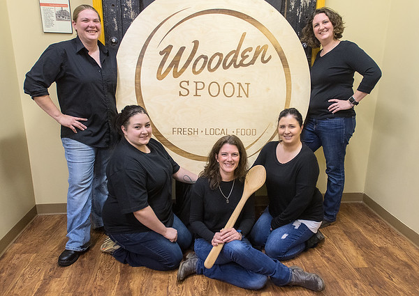From left, Brigette Rasmussen, Sam Cline, Natasha Frost, Samantha Rients and Nicole Lange in front of their new company logo. Wooden Spoon, which will open on January 2. Photo by Jackson Forderer