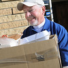 "John Cross<br /> Volunteer Duane ""Dewey"" Kruger leaves the Eagles Club with an armload of hamburger dinners bound for a Mankato-area business. It was expected that some 3,000 hamburger meals would be sold Friday during an annual Bite-A-Burger cancer fundraiser."