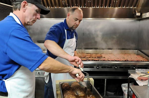 John Cross<br /> Dave Ewert (left) and Randy Ballman pull burgers from the grill during the 18th annual Mankato Eagles Club  Bite-A-Burger fundraiser on Friday.