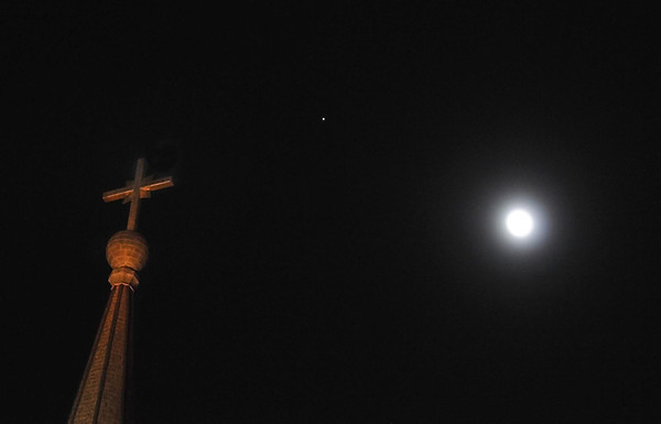 Pat Christman<br /> A nearly full moon and the planet Jupiter rise above the spire at St. Peter and Paul's Catholic Church Tuesday night.