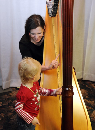 Pat Christman<br /> A young musician tries out Amy Kourteum's harp during Saturday's bridal show.