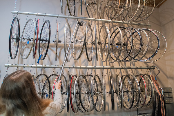 Key City Bike executive director Acacia Wytaske tries out an improvised hook to get wheels down from a rack in the nonprofit's new wheel room. With more space, bike parts are now more easily accessible to staff and volunteers. Photo by Jackson Forderer