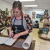 Design and Wine owner Laura Doyen helps her students by putting stencils onto sticky paper and cutting each piece off during a class at the store in Dec. 2017. Doyen said she holds private and public workshops that includes wood palette art, canvas painting, string art and mixed media. Photo by Jackson Forderer