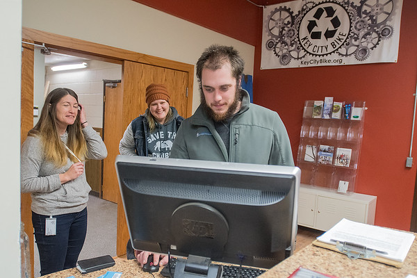 Matt Menze (right) logs in his volunteer hours at Key City Bike on Wednesday night. The nonprofit relies heavily on volunteer work and is now able to stay open year-round in their new building. Photo by Jackson Forderer