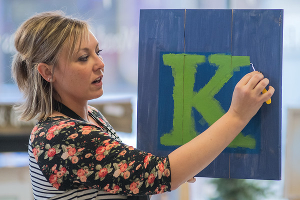 Laura Doyen, owner of Design and Wine, shows her students how to remove an outline of a stencil during a class at the store in Dec. 2017. The store on Belgrade Ave. in lower North Mankato opened in Sept. 2017, but Doyen said she has been doing private parties and classes since  Oct. 2014. Photo by Jackson Forderer