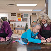 Shannon Schauer (right) gets help from her niece Kara Hinrichson, 9, while trying to apply a stencil to a piece of wood during a class at Design and Wine, as Beth Hinrichson tries to do the same with her stencil. Owner Laura Doyen has been teaching classes since Oct. 2014 but opened the storefront in lower North Mankato in Sept. 2017. Photo by Jackson Forderer