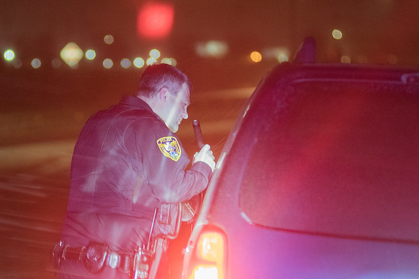 North Mankato Police Officer Mikeal Tordsen talks to the driver of a vehicle on Highway 14 during a traffic stop on Monday. Tordsen also works as an EMT for Gold Cross and handles medical calls while on patrol for North Mankato Police. Photo by Jackson Forderer
