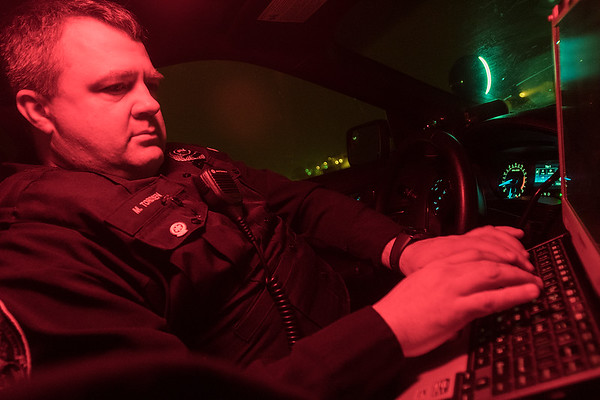 North Mankato Police Officer Mikeal Tordsen types on his laptop under a red dome light in his squad car during a traffic stop on Monday evening. Tordsen got his EMT certification in 2008 and he said about 27 percent of his calls are medical. Photo by Jackson Forderer