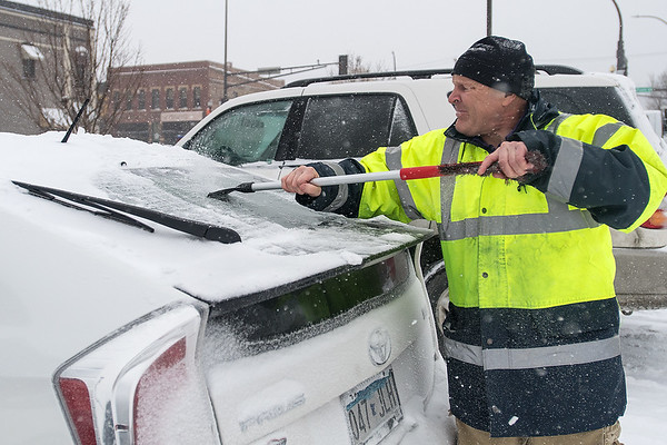 Mike Zwaschka scrapes ice off of his car as falling temperatures and heavy snow made driving conditions difficult on Friday. Photo by Jackson Forderer