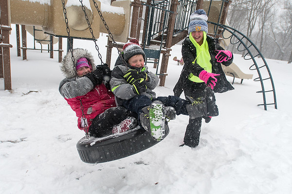 Lydia Huelsnitz (right), 12, pushes Parker Weckwerth (center), 5, and his sister Charlotte Weckwerth, 8, on a tire swing at Highland Park as snow fell on Friday afternoon. Most schools were let out early as a winter storm swept across Southern Minnesota. Photo by Jackson Forderer
