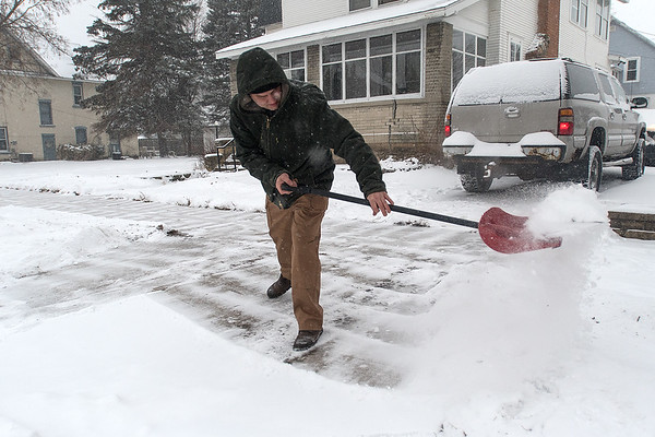 Josh Harvey shoves snow off of his driveway on Friday as a winter storm blanketed much of Southern Minnesota. Harvey said he was trying to stay ahead of the storm, shoveling more than once on Friday. Photo by Jackson Forderer
