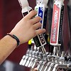 An employee taps a sample of beer for a visitor to the Mankato Brewery during Saturday's anniversary party.