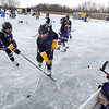 Two teams battle for the puck during a game at the Anthony Ford Memorial Pond Hockey Tournament Saturday on Lake Washington.