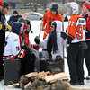 Teams stay warm around a fire on the ice on Lake Washington Saturday.