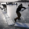 John Cross<br /> A volunteer wrestles with a pond hockey board in the wind Friday during set-up for today's fifth annual Anthony Ford Pond Hockey Tournament in front of Westwood on Lake Washington. The games begin at 8 .m.