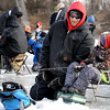 Ryan Augustin shows his son Dylan, 5, how to read the fish finder during the St. Peter Fire Department's youth fishing contest Saturday on Hallett's Pond.