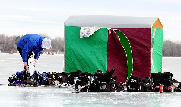 "Jake Miller puts on his shin pads outside their pond hockey team's ""warming house"" Saturday on Lake Washington."