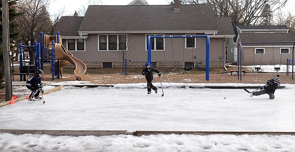 From left, Jonathon Sing, 8, Parker Wittenberg, 8, and his brother Jack, 10, play hockey on a rink in Mankato's Dotson Park. Jed Falgren, who lives across from the park, has been maintaining the popular rink since the city stopped doing it in 2003