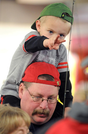 Pat Christman<br /> William Schultz, 3, reaches for his new fishing pole from atop his father Steve's shoulders Saturday.