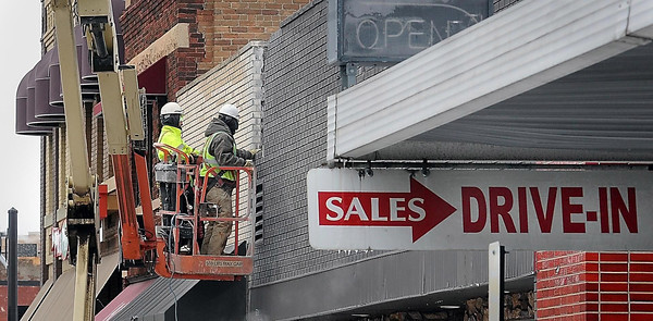 John Cross <br /> Workers remove bricks on the former Red Sky Lounge to isolate it from the adjacent Paglia's building along Front Street. The Red Sky building and the one that once housed Miller Motors are scheduled to be razed next week to make way for a $4.2 million project that will include a parking ramp along with a building housing apartments and several businesses. A seven-story, $7.85 million seven-story Profinium Tower already is under construction on the same block at the intersection of Warren and Riverfront.