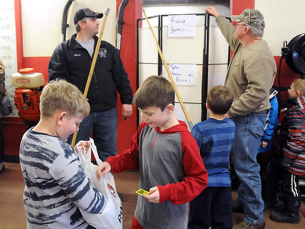 Pat Christman<br /> A pair of boys compare prizes after playing a fishing game at the St. Peter Fire Departments youth ice fishing contest Saturday at the fire hall. The event had to be moved indoors due to gusty winds.