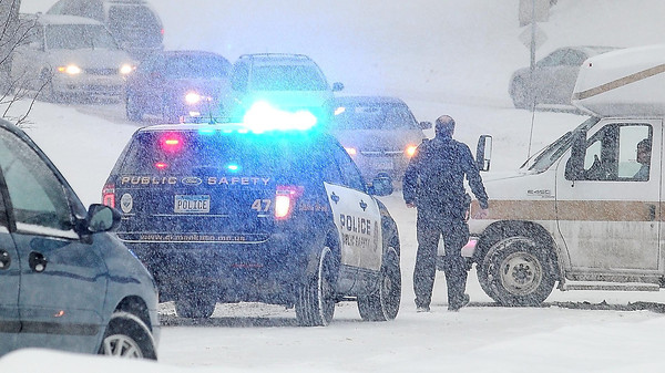 John Cross<br /> A  Mankato police officer watches traffic backup on Glenwood Avenue while assisting the driver of an MRCI bus that was blocking a traffic lane on Glenwood Avenue after getting stuck in the snow during the morning rush hour on Thursday.
