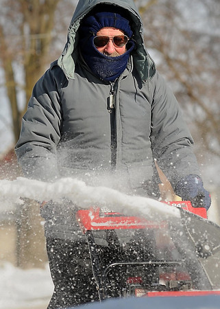 John Cross<br /> Bryan Rittenhouse may have had the day off from his position as a mail carrier on Monday, but he was still bundled against  the sub-zero  cold as he cleared his driveway and sidewalk of the aftermath of Sunday's blizzard.
