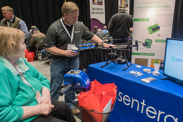 Joe Tinguely (center) with Sentera shows Carol Toreen (left) a drone during the Ag Expo held on Wednesday. The Ag Expo continues today at the Verizon Performance Hall in Mankato. Photo by Jackson Forderer