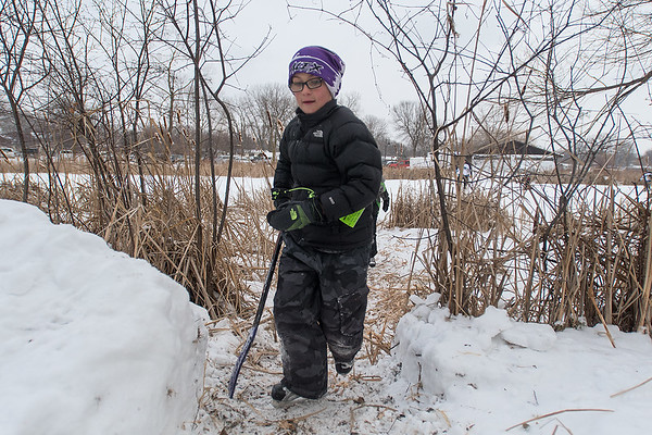 Alex Kunst, 9, walks through an opening in the brush while leaving Spring Lake at the conclusion of the Anthony Ford Pond Hockey Tournament held on Saturday. Photo by Jackson Forderer