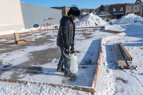 Dain Fisher sprays the edges and boards with water while preparing an ice skating rink at The Hub on Wednesday. Photo by Jackson Forderer