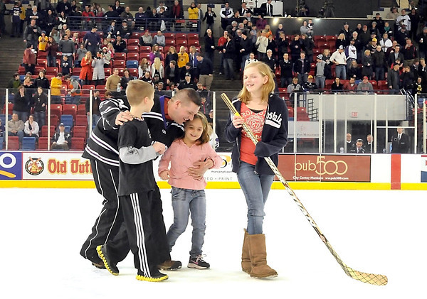 Nathan Lagred walks off the ice with his children (from left) Donovan, Gracia and Malia after seeing them for the first  time after returning from a 7-month deployment in Afghanistan at the MSU men's hockey game Friday night.