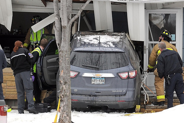 Rescue personnel work to free a man trapped in his vehicle after it crashed into a house at the corner of Warren Street and Balcerzak Drive Thursday afternoon.