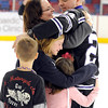 Capt. Nathan Lagred hugs his wife Juanita and his three children Malia, 10, Gracia, 5 and Donovan, 7 after surprising them by returning from a 7-month deployment in Afghanistan Friday at the Minnesota State University men's hockey game. His family was made to think they were taking part in a game during the first intermission by shooing at a goalie.
