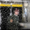 Champlin Auto Wash owner Doug Jurgens hoses off a car before it travels through the automated wash during a busy and warm Wednesday afternoon.