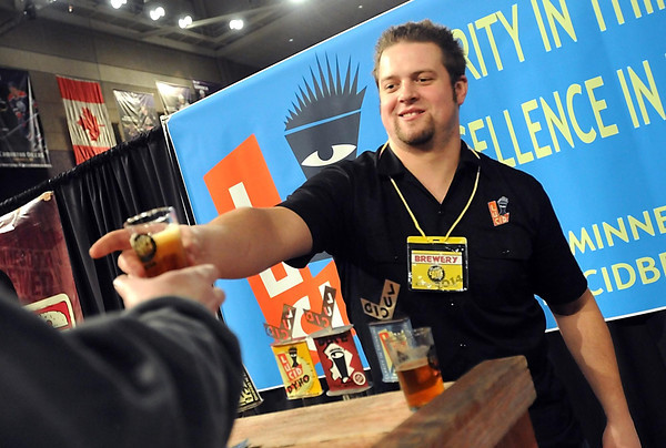 Pat Christman<br /> Mike Wehling hands a sample of Lucid Brewery's beer to a visitor to the Mankato Craft Beer Expo Saturday at the Verizon Wireless Center.