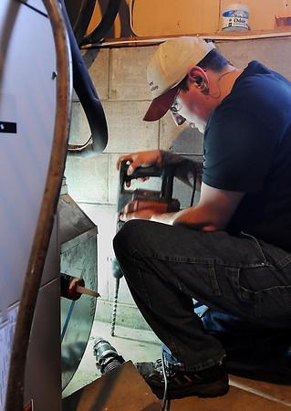 John Cross<br /> Dan Kelley bores holes through a basememt floor as part of a radon mitigation system installation.