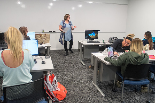 Jan Weber (center) teaches a practical nursing capstone class as Abbey Payton (right) helps out a classmate at Rasmussen College on Thursday. The college's new space includes large classrooms with computers that pop up from the students' tables. Photo by Jackson Forderer