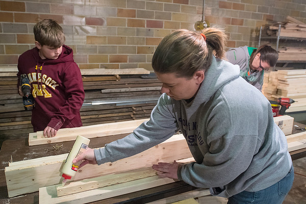"From left, Cameron Hanel, 11, Marie Hendrickson and Brenda Hanel assemble bed frames at Makerspace Mankato on Saturday. Organizer of the grassroots bed drive Jennifer Mason said, ""We will keep building until we've made enough for everyone that's asked."" So far, 66 beds have been donated to families in Mankato and surrounding communities. Photo by Jackson Forderer"