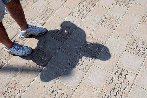 An attendee at the dedication of the Veterans Memorial Place views stones bearing the names of area veterans.