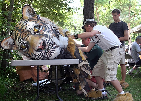 Chris Luttergardella shows Ben Groskreutz (foreground, in white) and Lukas Muszong how to work a puppet tiger suit during Saturday's Chautauqua in Waseca.