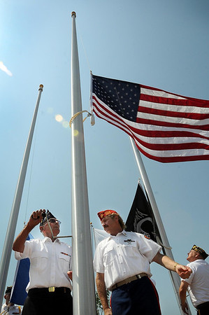 John Cross<br /> Don Stemper (left) and Pete Hagert raise the American flag during the dedication Wednesday of the Veterans Memorial Place.