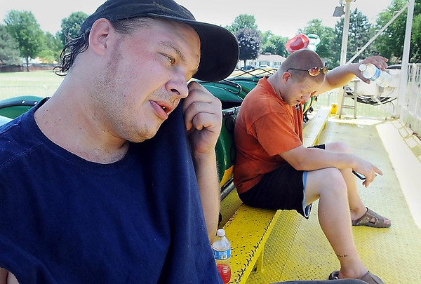John Cross<br /> It was a not-so-fun day Tuesday for Dave Lingl (right) and Adam Roemhildt as they took a break from setting up Family Fun carnival rides at Wheeler Park for North Mankato's Fun Days.