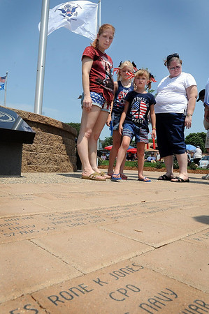 John Cross<br /> Juli Norell (left), daughters Maigan and Kitty, and their grandmother, Cyndi King view paving stones engraved with veterans' names prior to the dedication Wednesday of the Veterans Memorial Place.