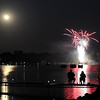 A couple sit on a dock as they along with hundreds of boaters watch a fireworks display on Lake Washington Tuesday night.