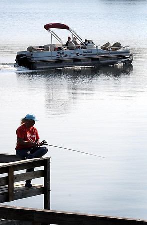 John Cross<br /> Sam Erickson of Mankato fishes from the public fishing pier on West Jefferson Lake as holidy boat traffic cruises by on Thursday.