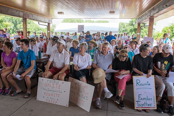 Attendees of the Keep Families Together rally try to stay cool in the shade at the pavilion in Riverfront Park. Over 300 people attended the rally held on Saturday to protest President Trump's policies of separating children from their parents at the border. Photo by Jackson Forderer
